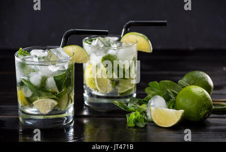Close-up view of mojito cocktail in glasses, mint and limes on black, cocktail drinks concept - Stock Photo