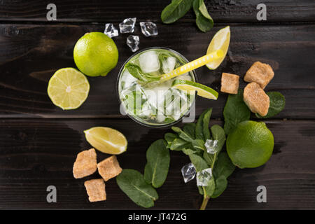 Top view of mojito cocktail in glass and fresh ingredients on dark wooden table top, cocktail drinks concept - Stock Photo