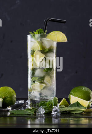 Close-up view of mojito cocktail in glass, sliced limes and mint on black, cocktail drinks concept - Stock Photo