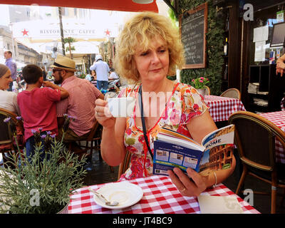 Rome Italy July 2017 - Female tourist reading a Lonely Planet guidebook about Rome - Stock Photo