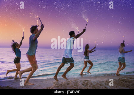 Happy smiling friends running at the beach with sparkling candles - Stock Photo