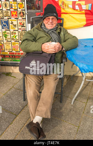 Senior male sitting outside a shop holding a mug in his hands on a winter's day. - Stock Photo