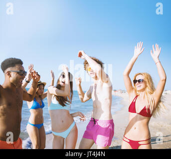 Group of friends dancing on the beach - Stock Photo