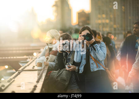 NEW YORK, USA - October 14, 2016. Group of Tourists Photographers on the Brooklyn Bridge during Sunset - Stock Photo