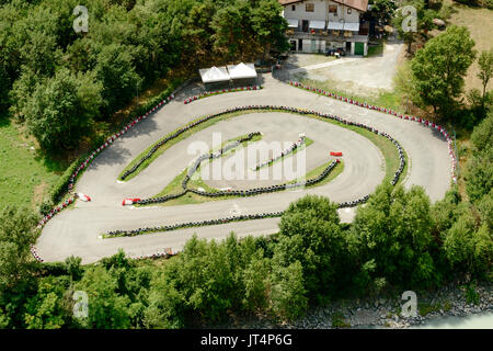 view from above of small racetrack near mountain touristic village, shot on a bright summer day at Chatillon, Aosta - Stock Photo