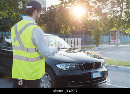 Police officer giving a ticket fine for parking violation - Stock Photo