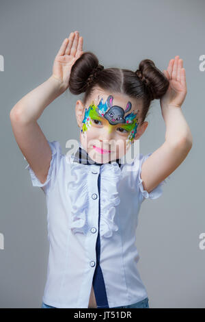 Little girl with a picture of the rabbit on the face on gray background - Stock Photo