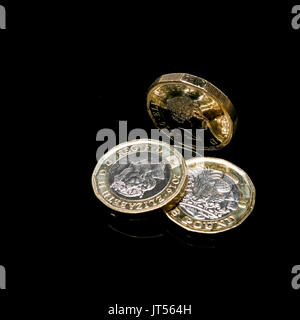 Three new One Pound coins on a black background - Stock Photo