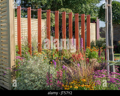 Pip Probert show garden 'For the Love of it' at the 2017 RHS Tattoo Flower Show.  Tall upright posts / planks provide - Stock Photo