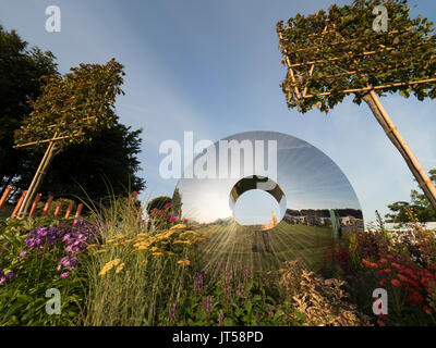 Pip Probert show garden 'For the Love of it' at the 2017 RHS Tattoo Flower Show.  A lawn leads into a colourful - Stock Photo