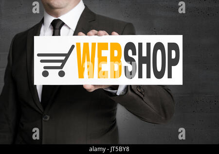 Webshop sign is held by businessman. - Stock Photo