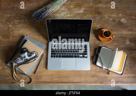 top view of laptop, diaries, vintage photo camera and cup of coffee on wooden tabletop - Stock Photo