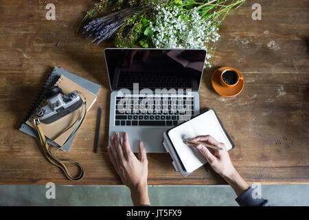 person using laptop and graphic tablet at workspace with notebooks and vintage camera - Stock Photo