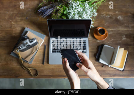 person using smartphone and laptop at workspace with notebooks and vintage camera - Stock Photo