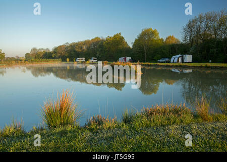 Caravans and campervan beside trees in rural landscape reflected in calm blue water of coarse fishing pond under - Stock Photo