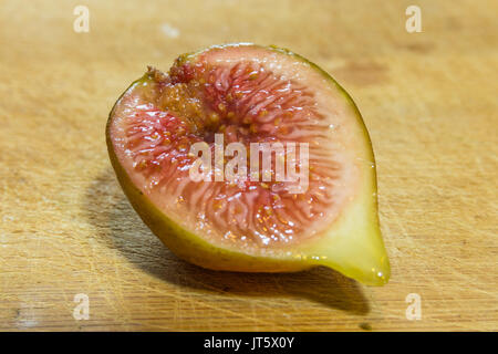 Horizontal photo of a close up on a half of a cut fig on a wooden cutting board - Stock Photo