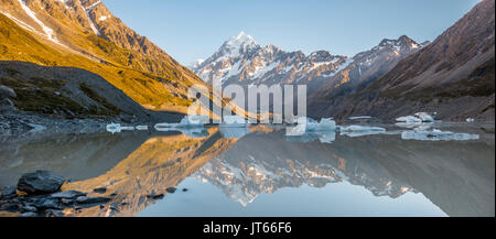 Sunrise, reflection in Hooker Lake, Mount Cook illuminated by morning sun, Mount Cook National Park, Southern Alps - Stock Photo