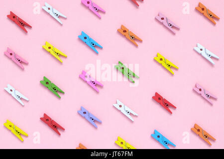 Colorful wooden clothespins on pink paper background - Stock Photo