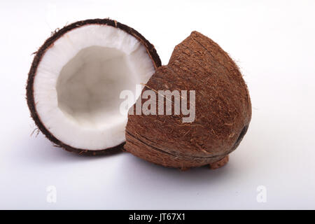 half of coconut top view of fresh broken coconut with shavings on black stock