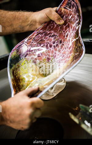 Man Working A Glass Blown Vase On Spinning Silica Sanding Disk Stock