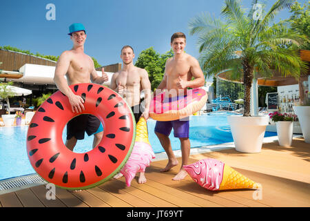 Smiling group of friends with rubber rings in front of a swimming pool. Young happy guys having fun and enjoying - Stock Photo