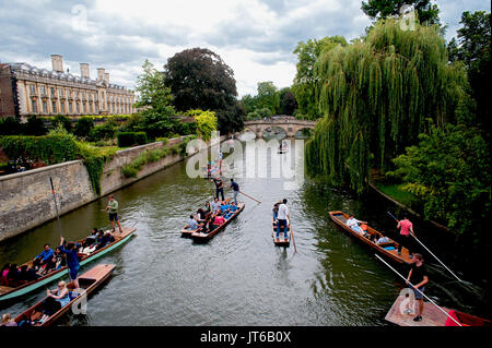 Tourists enjoying a punt along the River Cam passing under historic stone bridges and besides famous colleges of - Stock Photo