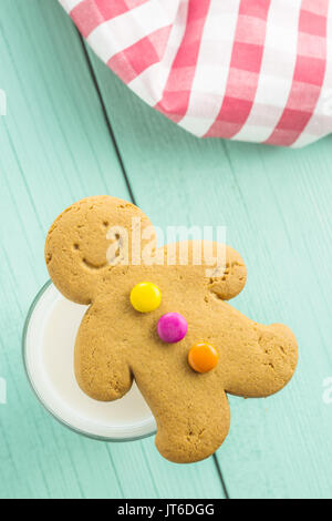 Sweet gingerbread man and glass of milk on wooden table. Xmas gingerbread. - Stock Photo