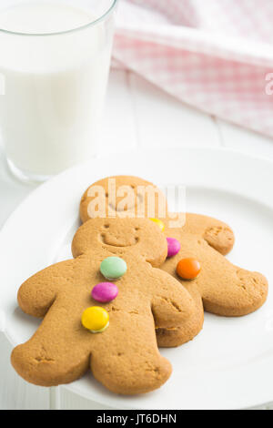 Sweet gingerbread men and glass of milk. Xmas gingerbread on white table. - Stock Photo