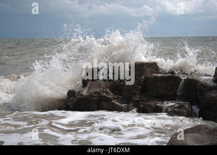 Waves break over the rocks as the tide turns to come in - Stock Photo