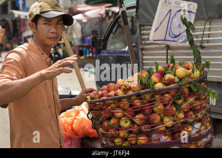 man vendor selling fruit on street in Saigon Vietnam - Stock Photo