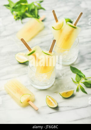 Summer refreshing lemonade popsicles with lime and mint in glasses with chipped ice, selective focus - Stock Photo