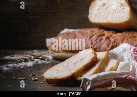 Homemade white wheat bread whole and slice served with wheat grain seeds and flour on white linen towel over dark - Stock Photo