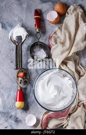 Ingredients and utensils for cooking meringue. Whipped egg whites, sugar powder, broken eggs, vintage sieve and - Stock Photo