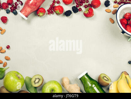 Green and red fresh juices or smoothies with fruit, greens, vegetables on grey background, top view, selective focus. - Stock Photo