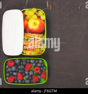 Sandwich, apple, grapes, carrot, berry in plastic lunch box on black chalkboard. Back to school concept. - Stock Photo
