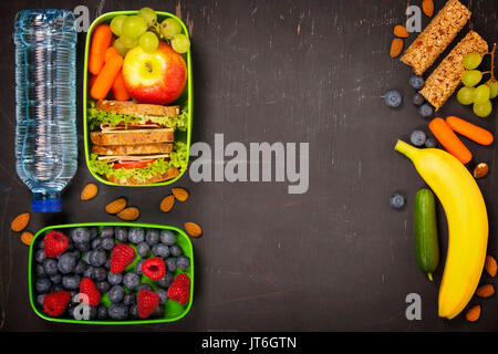 Sandwich, apple, grape, carrot, berry in plastic lunch box and bottle of water on black chalkboard. Back to school - Stock Photo
