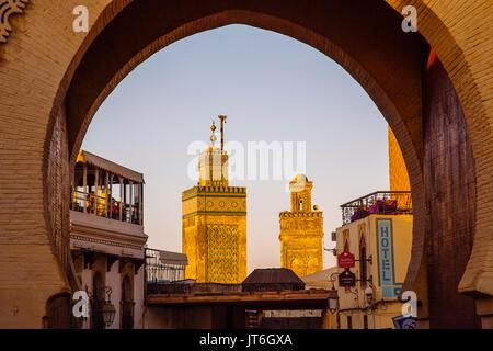 Street life scene. The Medersa Bou Inania minaret, Bab Bou Jeloud gate, main entrance to Souk Medina of Fez, Fes - Stock Photo