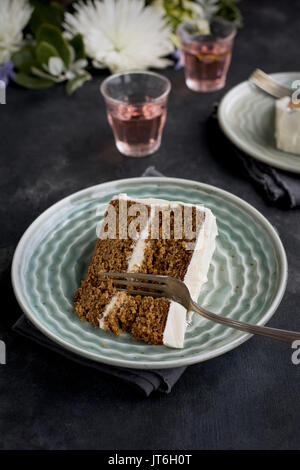 Marzipan Almond Cake with a Orange Blossom Mascarpone Frosting on a wooden pedestal, served with Rosé wine.  Photographed - Stock Photo