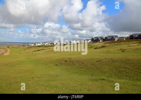 A sloping field beside the beach with some new build houses currently under construction giving a fantastic view - Stock Photo