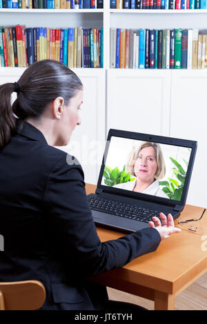 Rear view of a business woman in her office in front of her laptop, having a video call with her physician, telemedicine - Stock Photo