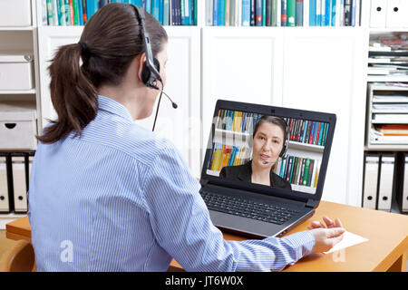 Rear view of a woman in a blue blouse with headset and laptop, having a live video call with her attorney, solicitor - Stock Photo