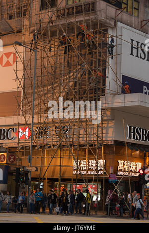 Construction workers build a bamboo scaffolding in the sunset on Nathan Road in Kowloon (Hong Kong) - Stock Photo