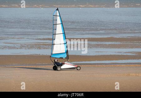 A pilot steers his land yacht along a sandy beach. - Stock Photo