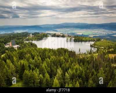 Glacial mountain lake Strbske Pleso in National Park High Tatras in Slovakia viewed from the olympic ski bridge - Stock Photo