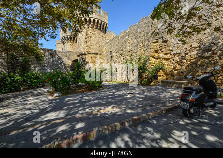 A black and white stray Greek cat relaxes in the shade with the ancient castle of Rhodes Greece in the background - Stock Photo