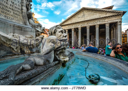 Closeup of the Fontana del Pantheon in the piazza della Rotonda as tourists sightsee with the ancient Pantheon in - Stock Photo