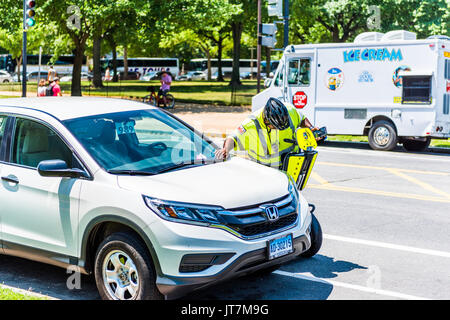 Washington DC, USA - July 3, 2017: Police traffic officer writing ticket for car illegally parked while riding segway - Stock Photo