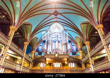 Montreal, Canada - May 28, 2017: Inside Notre Dame Basilica during mass with organ musical instrument and person - Stock Photo