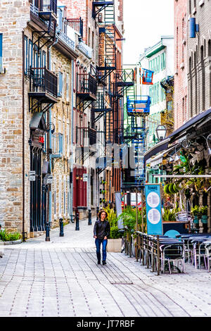 Montreal, Canada - May 28, 2017: Old town area with person walking in cobblestone alley during summer day in Quebec - Stock Photo