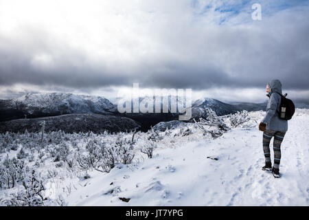 Young Woman Hiking High in the Mountains during Winter - Stock Photo